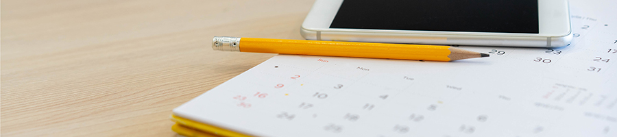 Phone and pencil lying on calendar